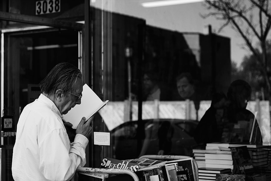 MAN READING AT BOOKSTORE, HENNEPIN AVE. MINNEAPOLIS MN